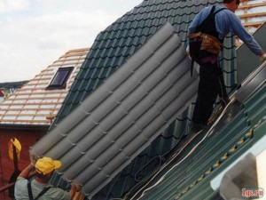 Строители тянут лист на крышу